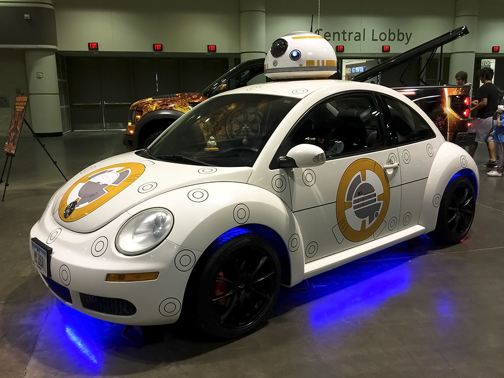 Custom BB-8 car painted white and orange and with a BB-8 dome on the roof